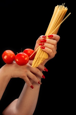 Female hands with beautiful manicure hold spaghetti and tomatoes on a black background Фото со стока