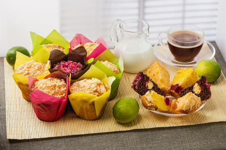 Color muffins in multicolored paper, with milk, a cup of coffee and limes on a mat from a bamboo and a cloth from rough fabric Фото со стока