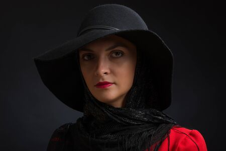 The young beautiful woman in a black hat with wide fields, an openwork scarf on a neck and a red dress