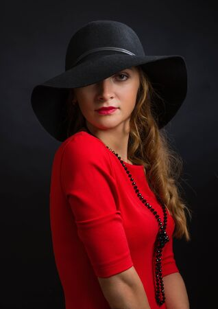 The beautiful young girl in a bright red dress and a black hat with the wide fields closing the right eye