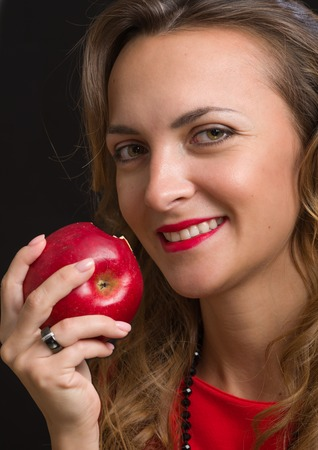 The young beautiful girl in a scarlet dress eats red apple