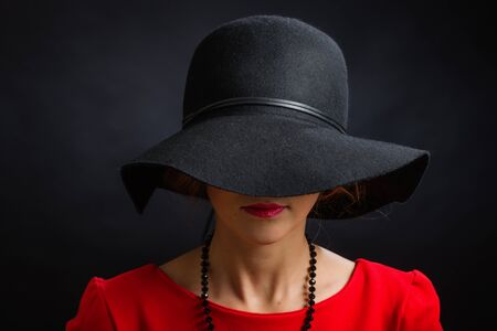 The beautiful young woman in a black hat with the wide fields closing eyes and a nose