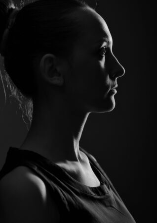 Silhouette of the young woman against a dark background