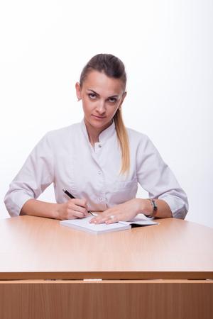 Молодая красивая женщина в медицинском костюме с ручкой в руке и ноутбук Фото со стока