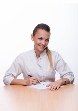 The young beautiful woman in a white medical suit with a pen in a hand and a notebook Фото со стока