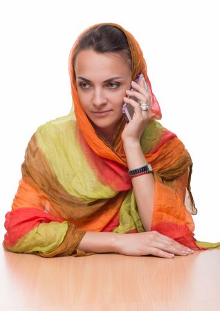 The beautiful young woman in a bright multi-colored shawl holds the mobile phone in hand