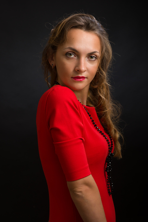The young beautiful woman in a bright dress of scarlet color with a black beads on a neck and ringlets against a dark background Фото со стока
