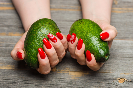Female hands with beautiful New Years manicure keep avocado fruits in style a rustic