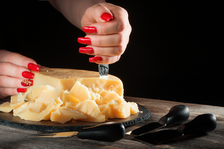 Female hands with bright beautiful manicure break away pieces of hard cheese like parmesan by means a special knife