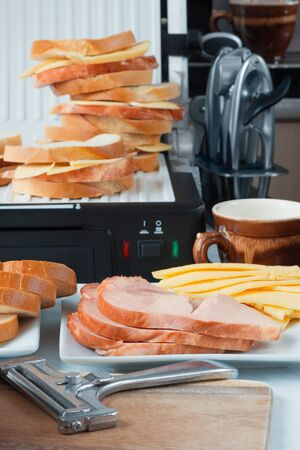 Hot cheese and ham sandwiches, a  slicer, cup of coffee slices