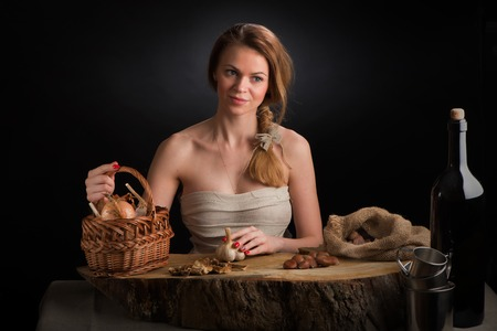The young beautiful girl in a sundress from  canvas sits at an oak table with  garlic head in  hand near  basket  onions and  bag  chestnuts Фото со стока