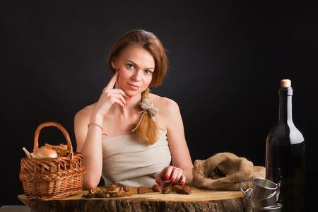 Молодая красивая девушка в сарафане с холста сидит на дубовом столе о корзине с луком и чесноком, сушеные шампиньоны