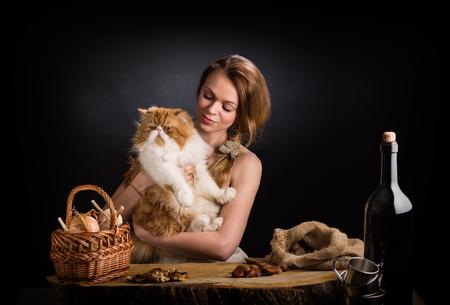 Молодая красивая девушка в сарафане с холста сидит на дубовом столе с замечательным красным персидским котом на руках возле корзины лука, сушеных грибов и каштанов мешка Фото со стока