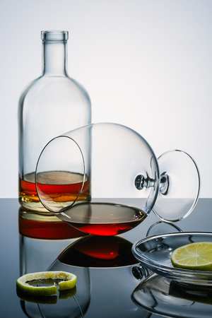Glasswares winh the alcohol remains, pieces and a peel of a lime on the reflecting surface