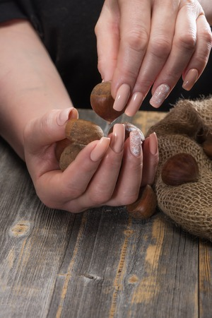 Female hands with beautiful magnificent manicure shift chestnuts from a linen bag on wooden boards