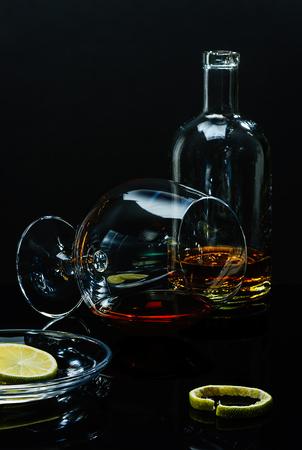 Бутылка и стакан с остатками алкогольного напитка, блюдце с известковыми кусочками