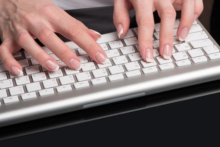 Женские красивые руки с классическим французским маникюром расположены над компьютерной клавиатурой