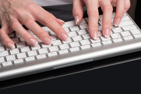 Female beautiful hands with classical French manicure are located over the computer keypad
