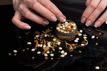 Женские руки с красивым французским маникюром собирают фасоль, разбросанную на черном фоне, горох, сушеные овощи и специи в старинном мелхиоровом солонке