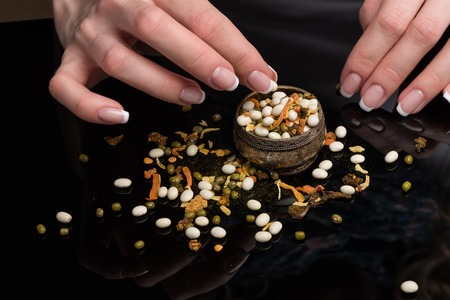 Female hands with beautiful French manicure gather the haricot scattered on a black background, peas, dried vegetables and spices in a vintage melkhiorovy saltcellar