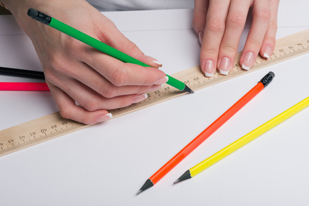 Female hands with classical French manicure draw a pencil by means of a ruler on clean standard sheet