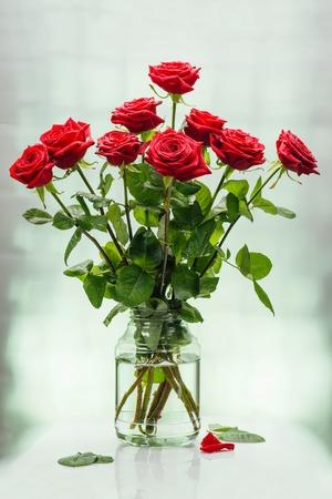 Букет из алых великолепных роз в банке с водой на светлой поверхности Фото со стока