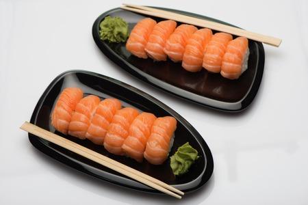 Лососевые суши, деревянные палочки и васаби на двух черных керамических плитах бобовидной формы