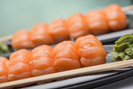 Суши со слабосоленым лососем, деревянными палками и соусом васаби на керамической темной плите