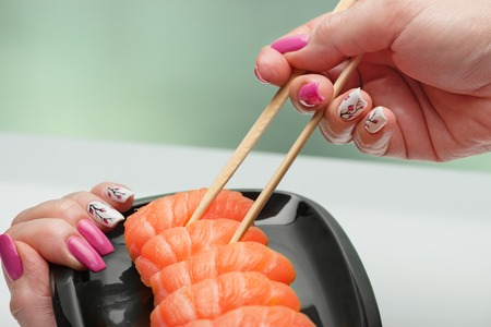 The female hand with magnificent manicure takes sushi with a light-salted salmon from a black plate by means of wooden sticks Фото со стока
