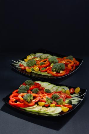 Красиво и аппетитно вырезать свежие овощи и капусту из брокколи на двух черных керамических плитах