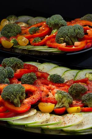 Красиво и аппетитно вырезать свежие овощи и капусту из брокколи на двух черных керамических плитах закрыть
