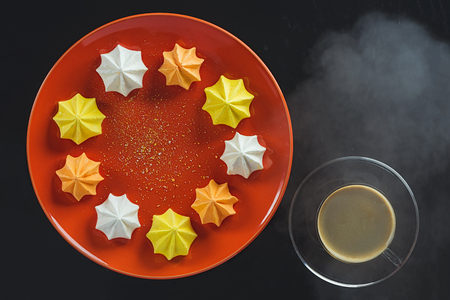 Multi-colored figured cookies on a round orange plate and a cup of hot coffee on a black background Фото со стока