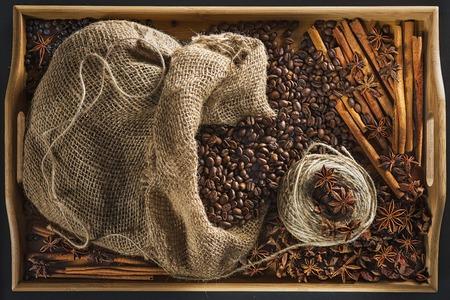 Бельевая сумка с кофейными зернами, кусок веревки, палочка корицы, ягода можжевельника и плоды анисетри на подносе из бамбука