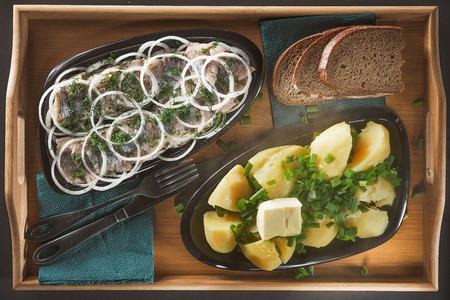 Кусочки сельди с кольцами из лука и фенхеля, картофель с зеленым луком и кусок масла на двух керамических плитах из яйцевидной формы на деревянном подносе из бамбука Фото со стока