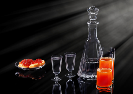 Decanter and two shot glasses with ice vodka, two salmon red caviar sandwiches on a glass plate and two glasses with multifruit juice on a black acrylic surface Фото со стока