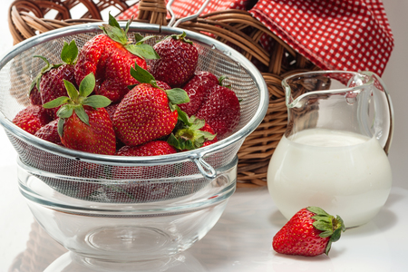 Ripe fresh strawberries in a colander and milk cream in a glass jug