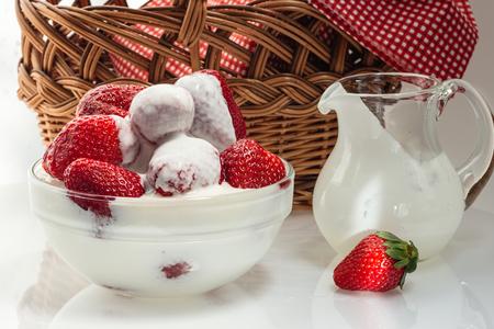Спелая свежая клубника в чашке с молочным кремом