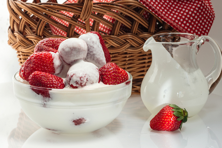Ripe fresh strawberries in a cup with milk cream Фото со стока