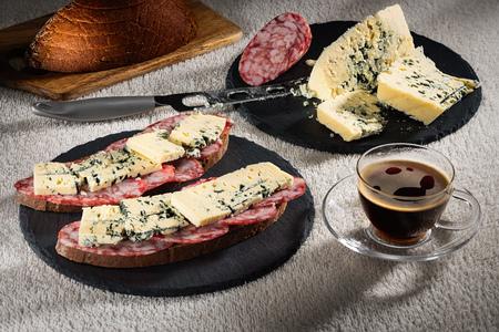 Бутерброды с сыром Дорблю и сырой копченый колбас на черных листах сланца, сырный нож и чашка горячего кофе