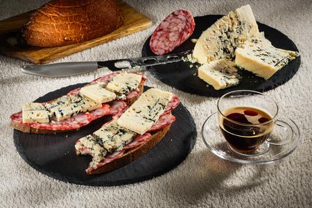 Два бутерброда из черного хлеба с сыром Дорблу и сырой копченой колбасой на черных листах сланца, сырный нож, деревянная разделочная доска с хлебом и чашка горячего кофе на прозрачной тарелке из стекла
