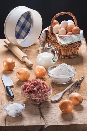 Кусочки кухонной утвари и набор продуктов для приготовления пельменей и пельменей на столешнице из дуба