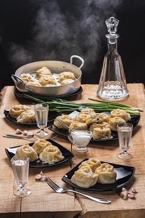 Готовые горячие манти на черных тарелках, водка в графине и три свая на столешнице из дуба