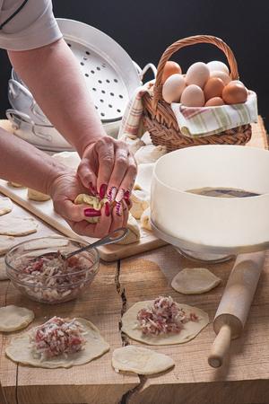Женские руки с красивыми маникюрными пельменями на столешнице из дуба Фото со стока