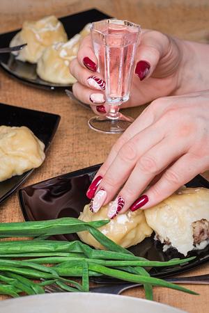 Женская рука с красивым маникюром держит стакан с водкой Фото со стока