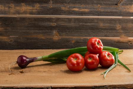 Зеленый лук и помидоры на фоне старых досок Фото со стока