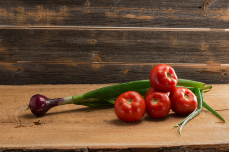 Green onions and tomatoes against the background of old boards
