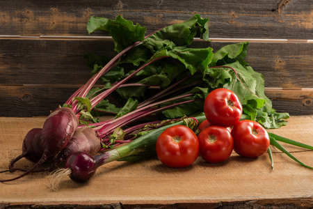 Green onions, beet and tomatoes against the background of old boards Фото со стока