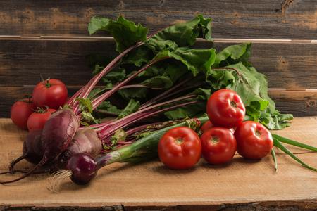 Зеленый лук, свекла и помидоры на фоне старых серых досок