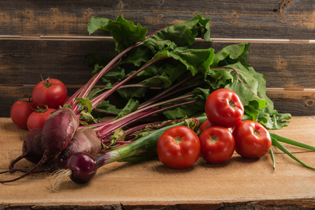 Green onions, beet and tomatoes against the background of old grey boards