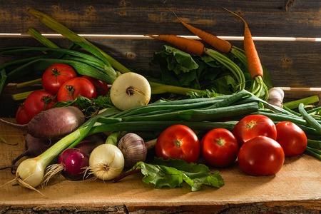 Зеленый лук, чеснок, морковь, свекла и помидоры на фоне старых серых досок Фото со стока